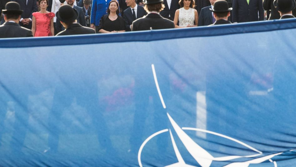 Leaders of NATO member countries watch a performance in front of a blue NATO flag.