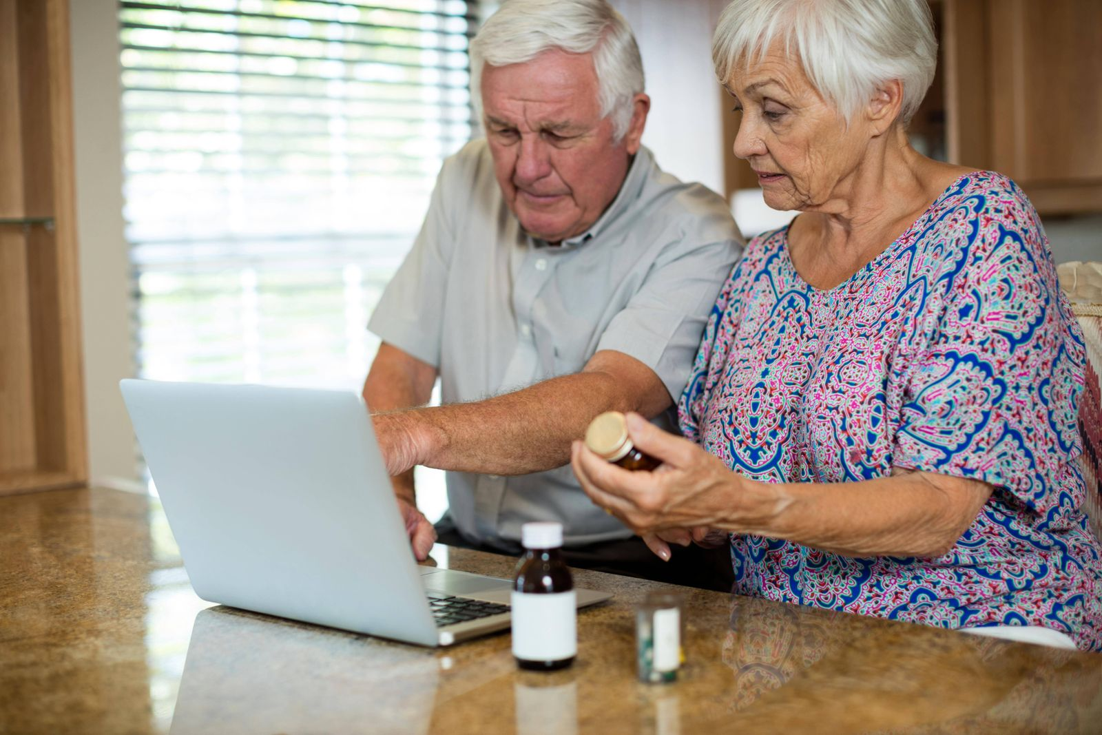 Senior couple using laptop and holding pill bottle in kitchen model released Symbolfoto property