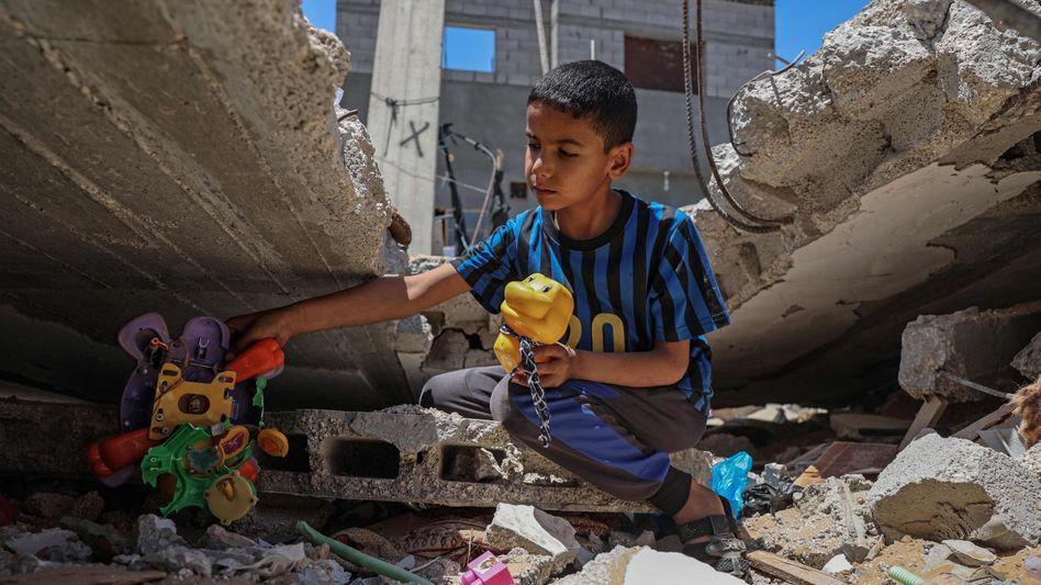 Ein Junge spielt in den Trümmern in Gaza
