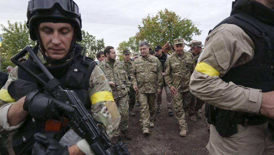 """Der ukrainische Präsident Poroschenko (Mitte) mit Soldaten: Kein """"Terrorist"""" soll seiner Verantwortung entgehen"""