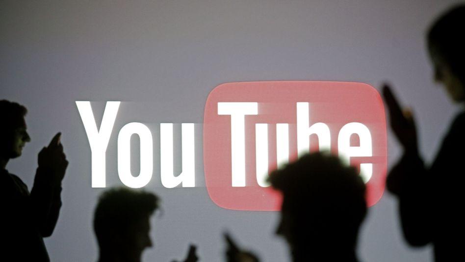 Smartphone-Nutzer vor YouTube-Logo