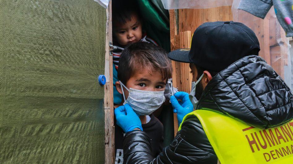 Ein Helfer kümmert sich im Camp Moria um einen kleinen Jungen