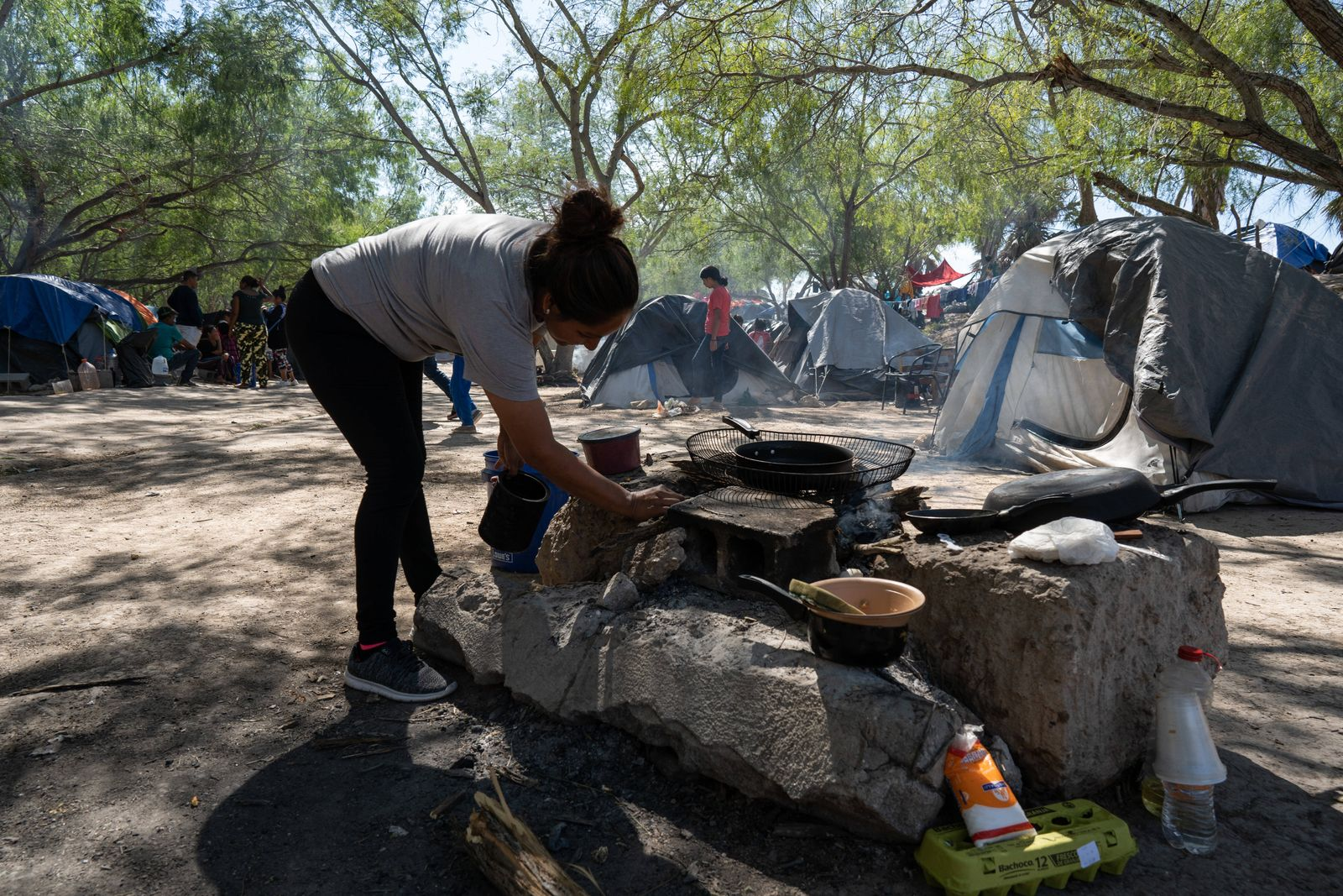 Mexico Refugees Matamoros, Mexico, 01 November 2019, a woman is seen tending to a stove in the refugee camp site. Around