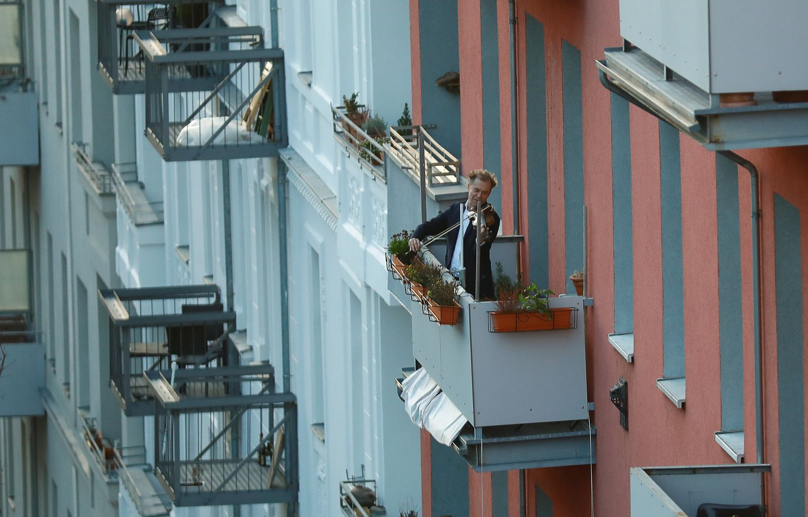 A man plays the violin from a balcony to raise morale in Berlin