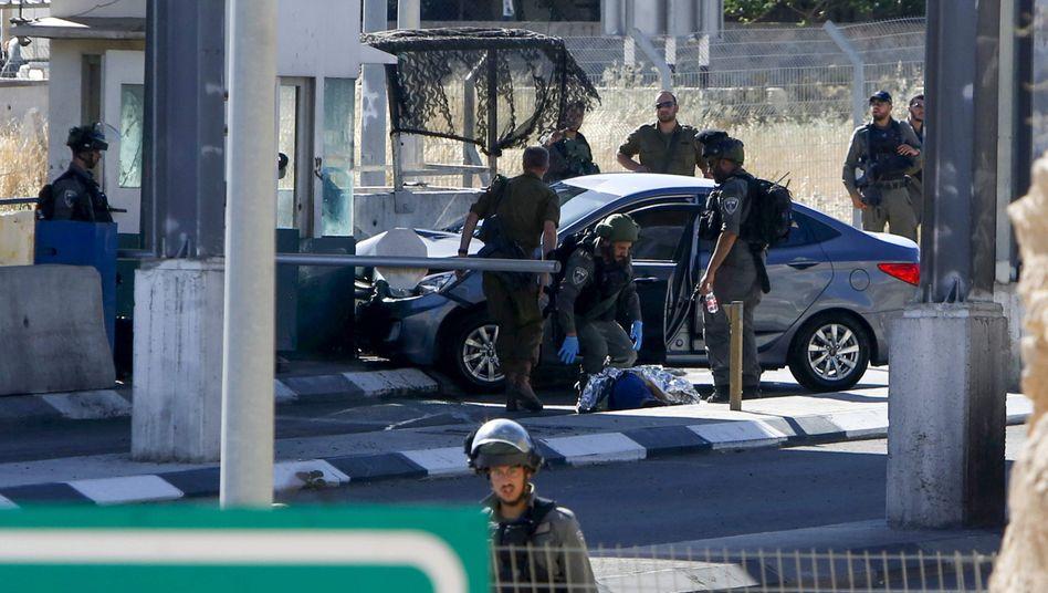 Israelische Soldaten bei der Leiche des toten Palästinensers