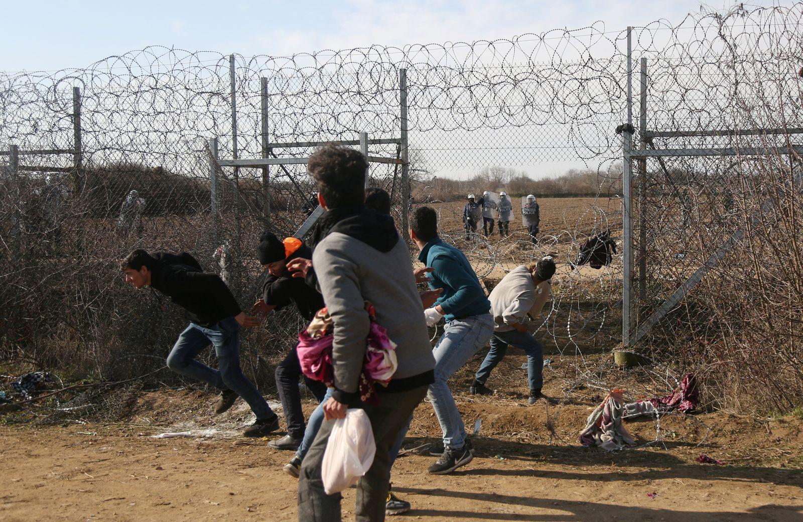 Migrants throw stones at a Greek military vehicle on the Turkish-Greek border at Turkey's Pazarkule border crossing with Greece's Kastanies, near Edirne