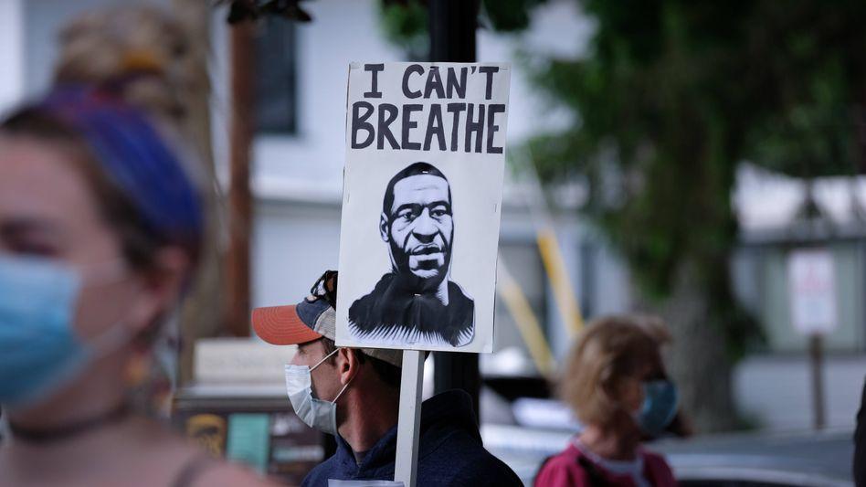 """Demonstranten mit Plakat zum Gedenken an George Floyd: """"Erstickung durch anhaltenden Druck als Todesursache"""""""