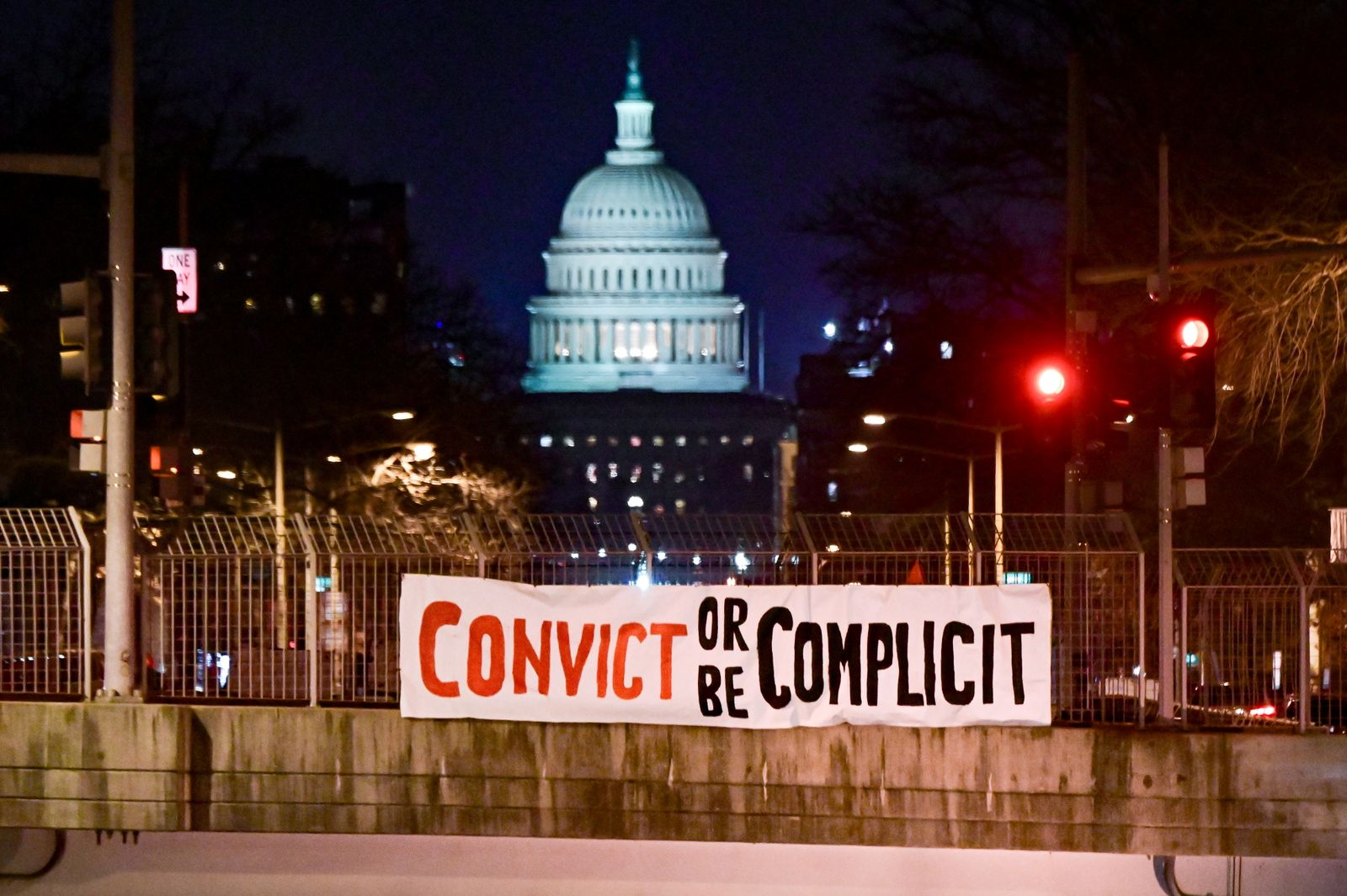 """A banner reading, """"Convict or be complicit"""" is hung over a bridge in view of the U.S. Capitol on the first day of the Senate impeachment trial against former President Donald Trump in Washington"""