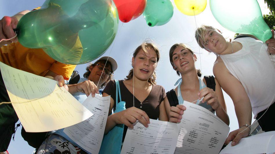 Schülerinnen mit Zeugnissen (Archivbild): Sind Zensuren sinnvoll oder nicht?