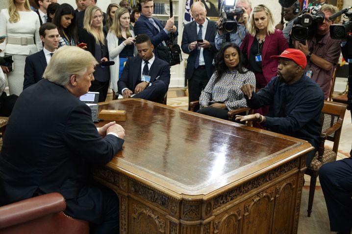 11.10.2018, USA, Washington: US-Rapper Kanye West (r) spricht während eines Treffens mit Donald Trump (2.v.l), Präsident der USA, im Oval Office des Weißen Hauses. Neben Trump sitzt sein Berater Jared Kushner (l). Foto: Evan Vucci/AP/dpa +++ dpa-Bildfunk +++  