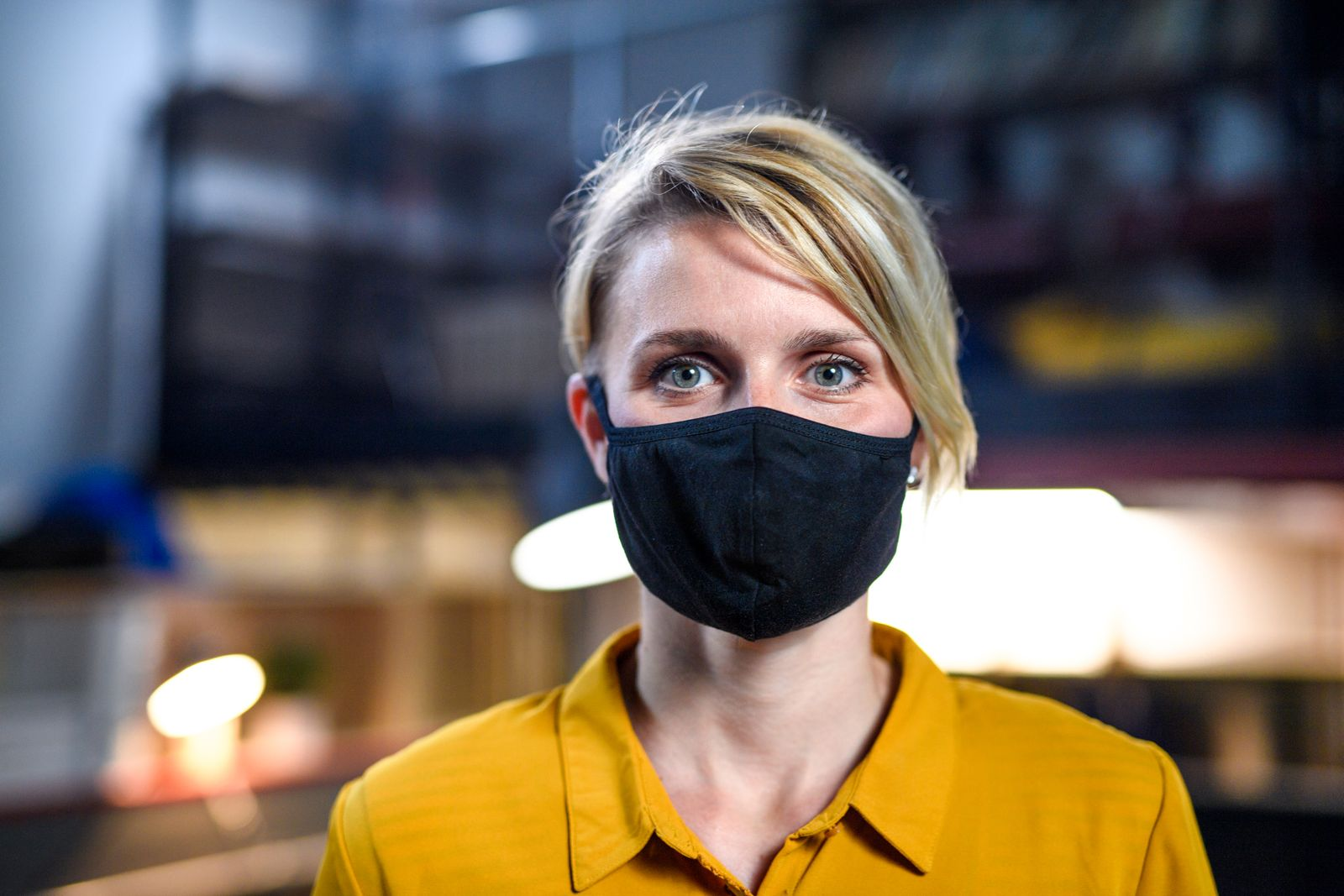 Portrait of woman with face mask standing indoors in office, looking at camera.