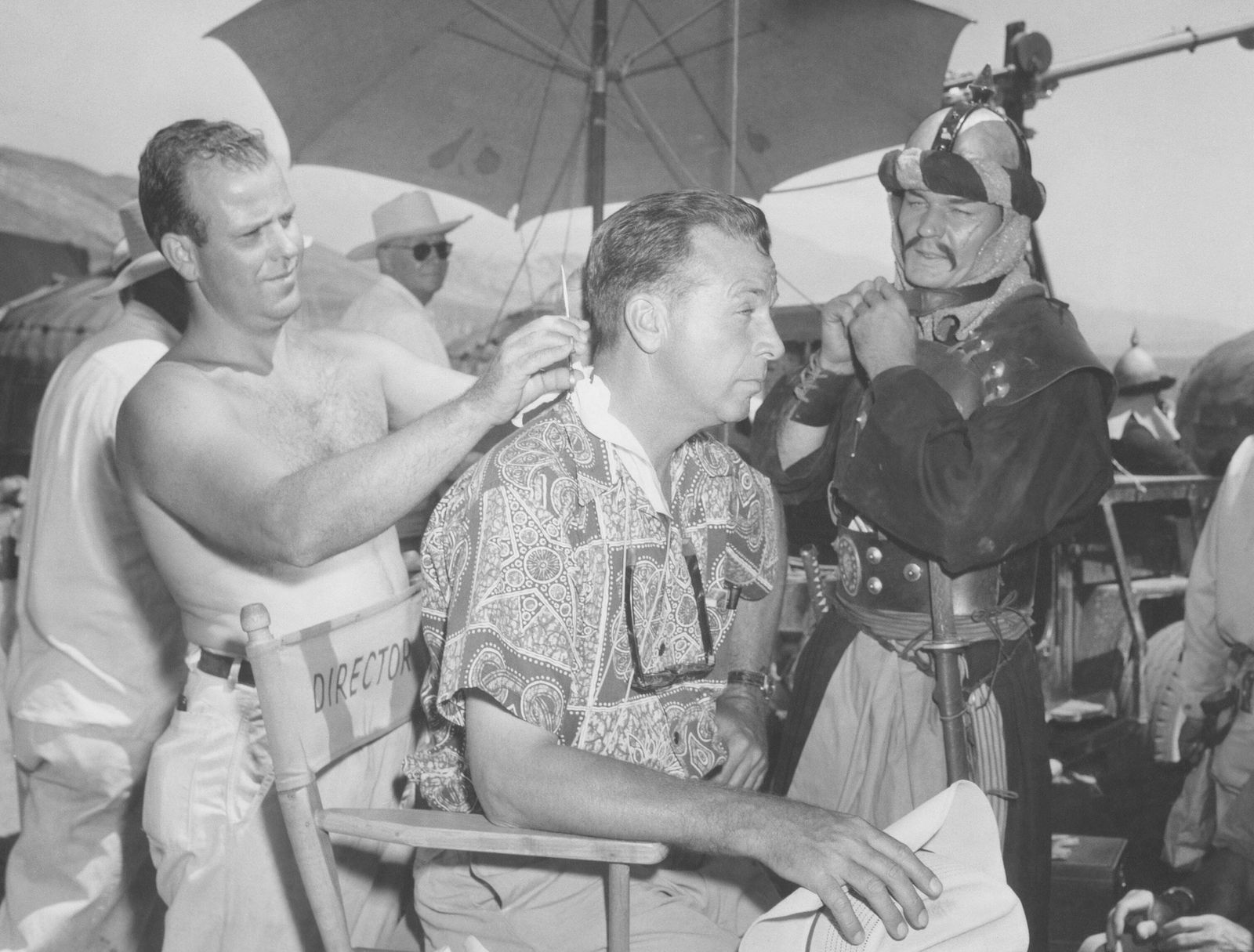 THE CONQUEROR, from left: makeup man Jimmy House cuts director Dick Powell s hair as Leo Gordon looks on, 1956 !ACHTUNG