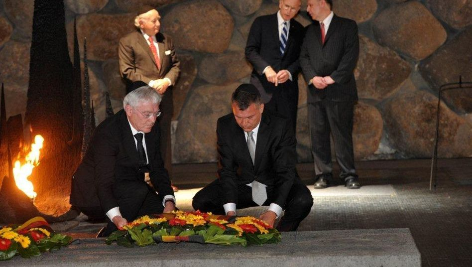 German Finance Ministry officials lay a wreath at Yad Vashem in Jerusalem, as Claims Conference negotiators look on.