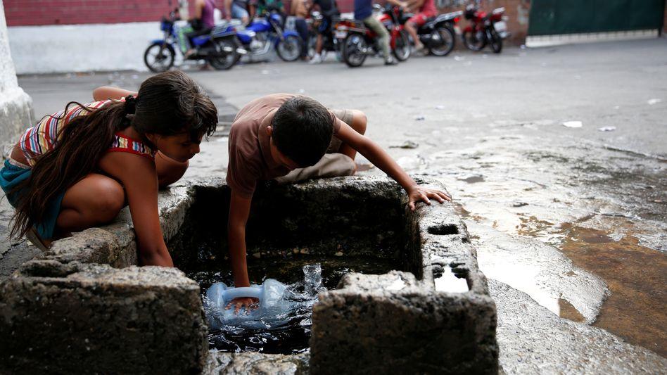 Kinder füllen einen Wasserkanister in Caracas, Venezuela