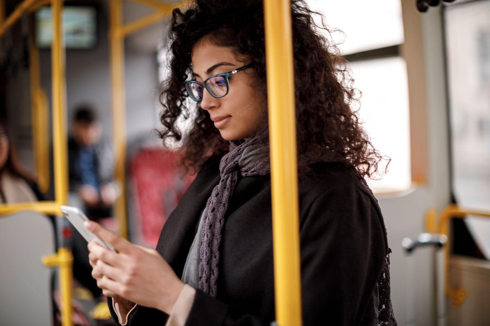 Young woman traveling by bus and using smart phone