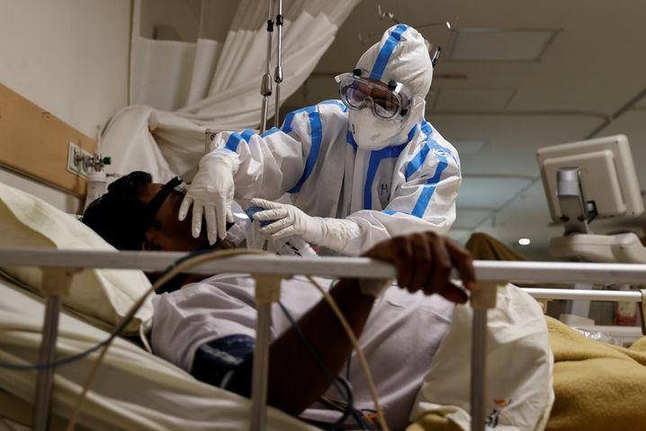 Ein Pfleger versorgt einen Corona-Kranken in Neu-Delhi. Ein Video aus einem Krankenhaus in Mumbai zeigt dagegen Patienten, die auf Kartons auf dem Boden schlafen müssen.