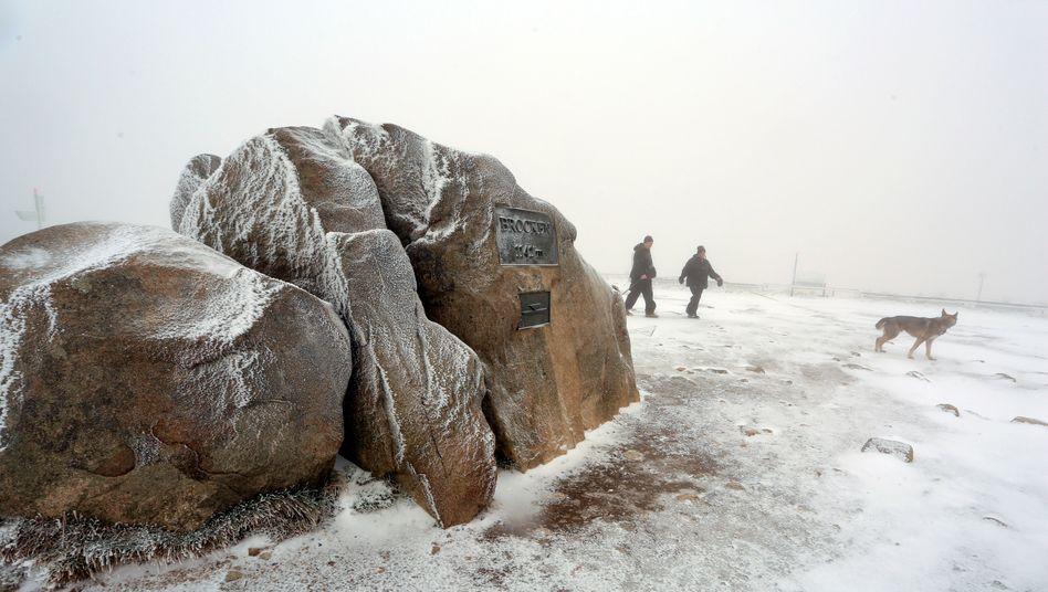 Erster Schnee der Saison: Wanderer gehen am höchsten Punkt auf dem Brocken entlang