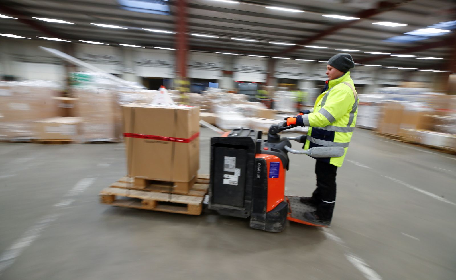 A female employee of German postal and logistics group Deutsche Post DHL moves freight with a pallet transporter at a DHL freight logistics centre in Sehlem