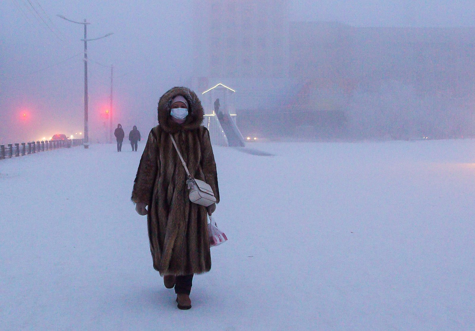 YAKUTSK, RUSSIA - DECEMBER 13, 2020: A local woman walks in Lenin Square in freezing conditions of minus 43 degrees Cels