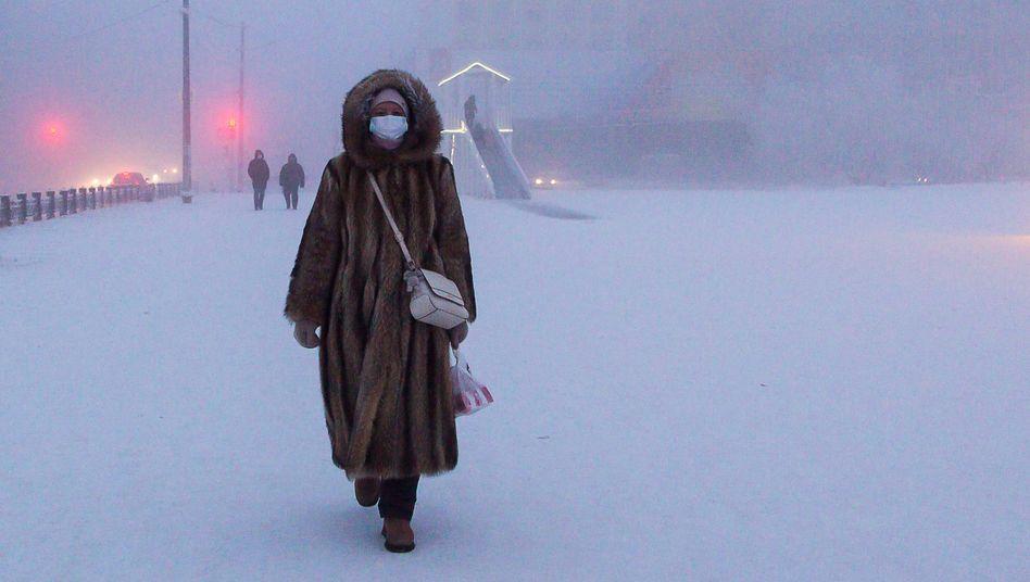 Eine Frau mit Maske und Fellmantel in Jakutsk