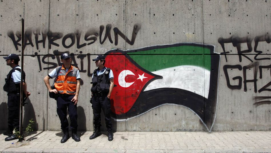 Turkish riot police stand in front of pro-Palestinian graffiti near the Israeli Consulate in Istanbul on Tuesday.