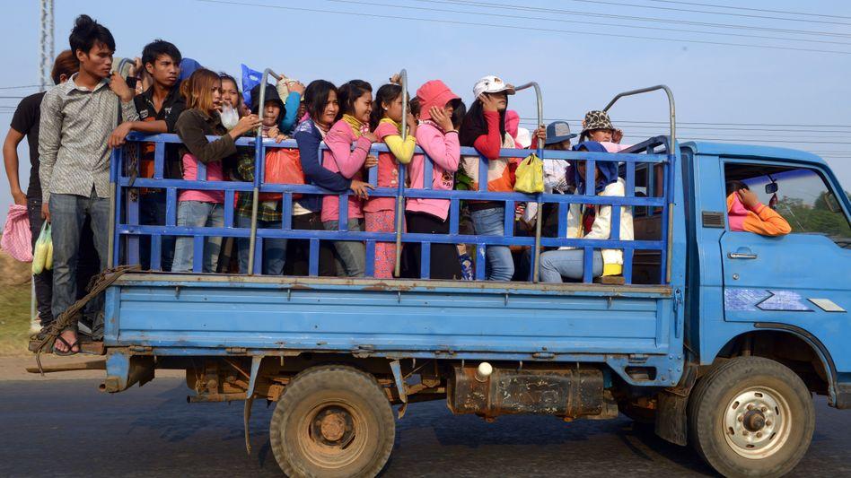 Textilarbeiter bei Fahrt in Fabrik bei Phnom Penh: Wichtige Exportindustrie