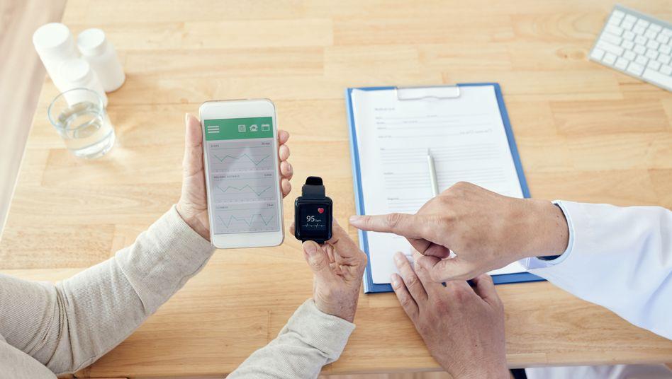Eine ältere Patientin bespricht mit ihrem Arzt Gesundheitswerte auf dem Smartphone (Symbolbild)