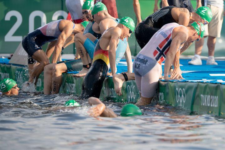 Die Sportler kommen nach dem Fehlstart aus dem Wasser