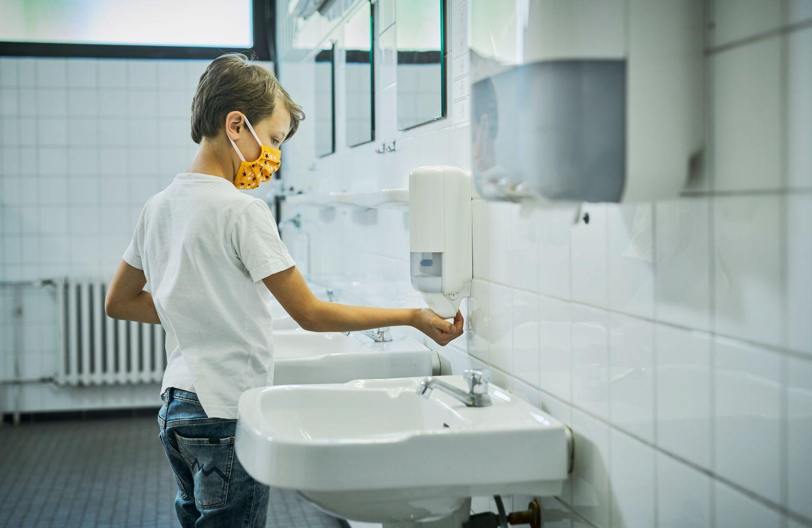 Boy wearing mask on school toilet washing his hands