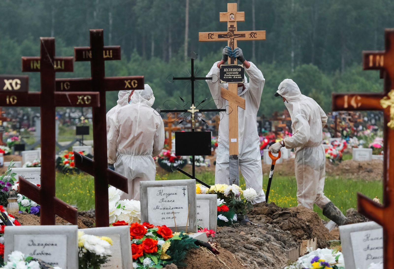 Grave diggers wearing personal protective equipment (PPE) bury a person, who presumably died of the coronavirus disease (COVID-19) in the special purpose section of a graveyard on the outskirts of Saint Petersburg