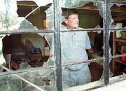 Zimbabwean farmer Paul Retzhoff looks out of the broken windows of his farm office and storeroom at his homestead on Lonely Park farm 30 Km's east of Harare. War veterans who attacked the homestead and smashed windows and broke into the house stealing food and alcohol were chased away by farm labourers from Retzhoff's and neighboring farms.