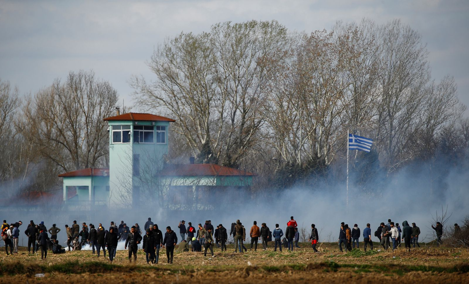 Migrants stand near a cloud of tear gas as they gather on the Turkish-Greek border near Turkey's Pazarkule border crossing with Greece's Kastanies