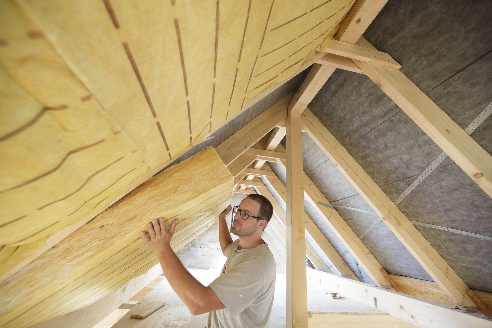 Ein Mann kleidet einen Dachstuhl mit einer Innenraumdaemmung aus Model Release vorhanden model rel
