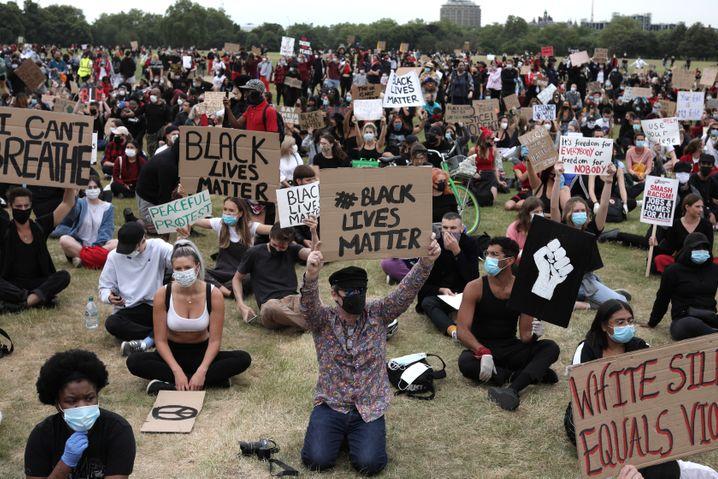 Demonstranten mit Gesichtsmasken und Plakaten im Londoner Hyde Park