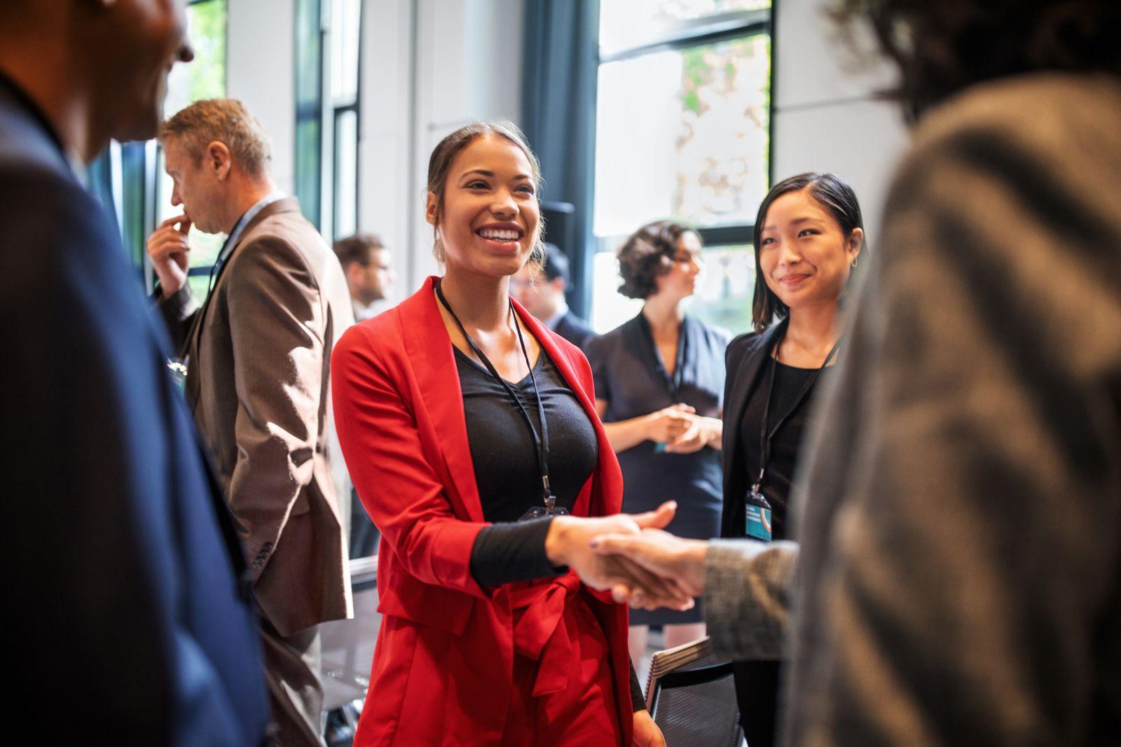 Businesswomen handshaking in auditorium corridor
