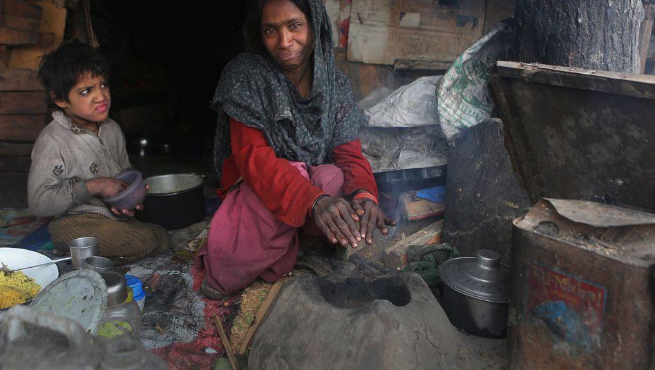 Menschen vor Kleinofen in Srinagar (Indien): Die meisten Schadstoffe sind selbst produziert