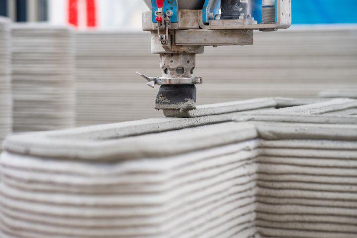 Eine Düse trägt Mörtel und Beton auf