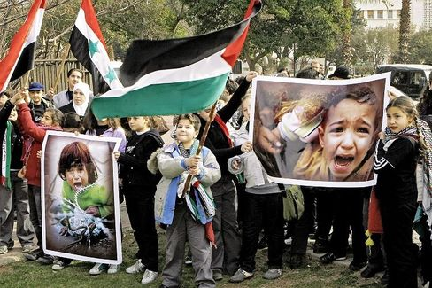 Syrian children carry Palestinian and Syrian flags along with pictures of crying children during a sit-in protest against Israel's military offensive in the Gaza Strip.