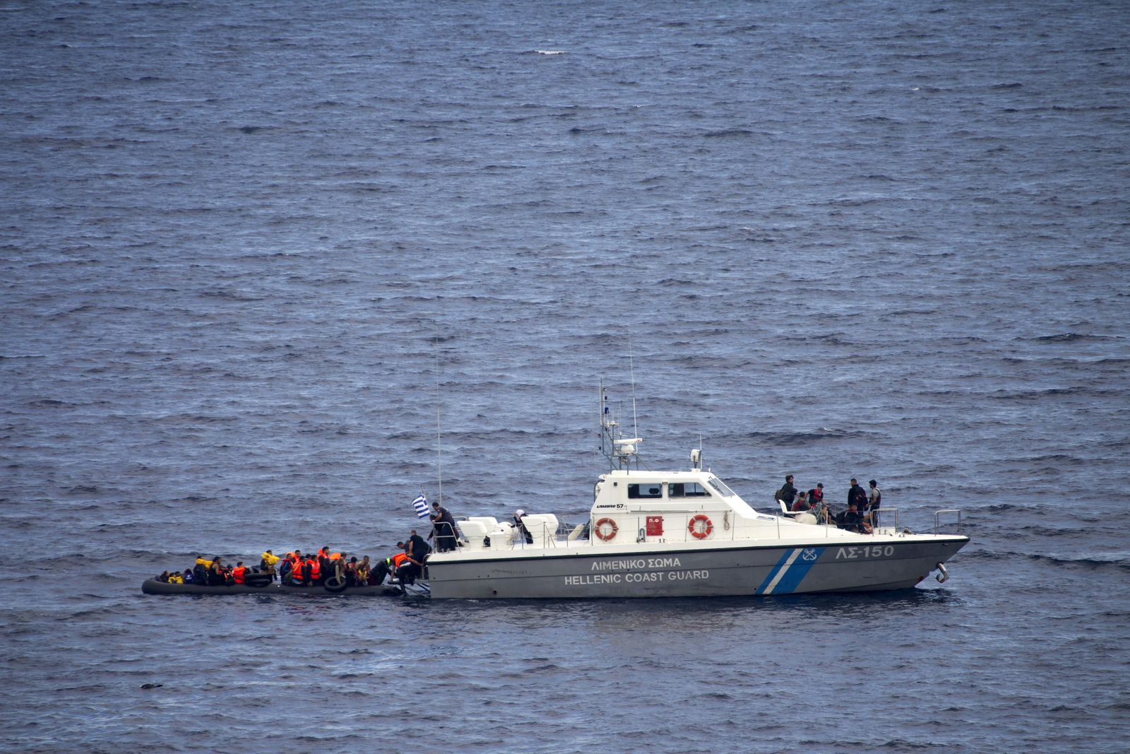 A Greek coast guard vessel approached an overcrowded dinghy carrying refugees and migrants during their effort to reach the Greek island of Lesbos by crossing a part of the Aegean Sea from the Turkish coast