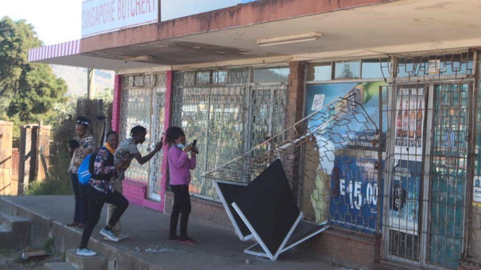 Menschen fotografieren ein beschädigtes Geschäft in Eswatinis Hauptstadt Mbabane (Foto vom 29. Juni)
