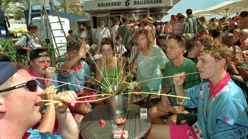 German tourists at the legendary Balneario No. 6 bar in Palma de Mallorca sip a mix of sangria, vodka, rum and soda from a common bucket.