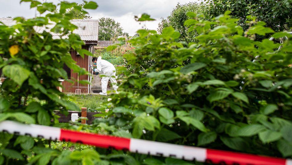 Ein Polizeibeamter der Spurensicherung steht in der Kleingartenkolonie vor der Laube des mutmaßlichen Haupttäters (Archivbild)