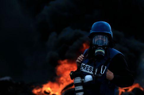 Ein palästinensischer Fotograf steht vor brennenden Reifen während Zusammenstößen zwischen palästinensischen Demonstranten und israelischen Streitkräften im Dorf Kfar Qaddum, nahe der Stadt Nablus