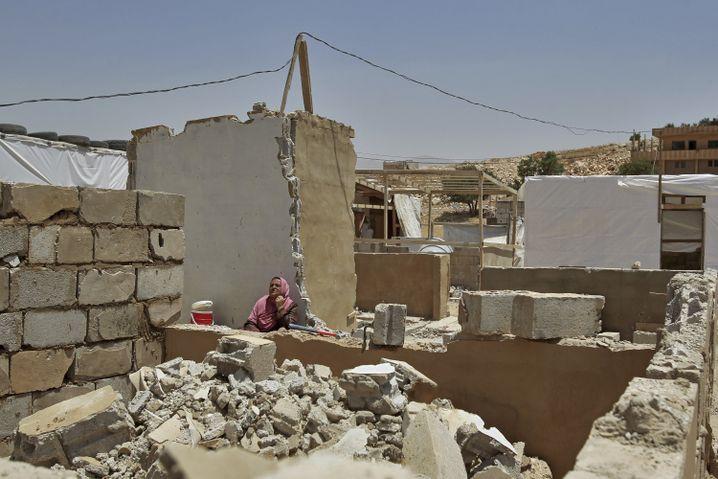 Syrische Flüchtlingsfrau zwischen den Trümmern ihres abgerissenen Hauses in Arsal