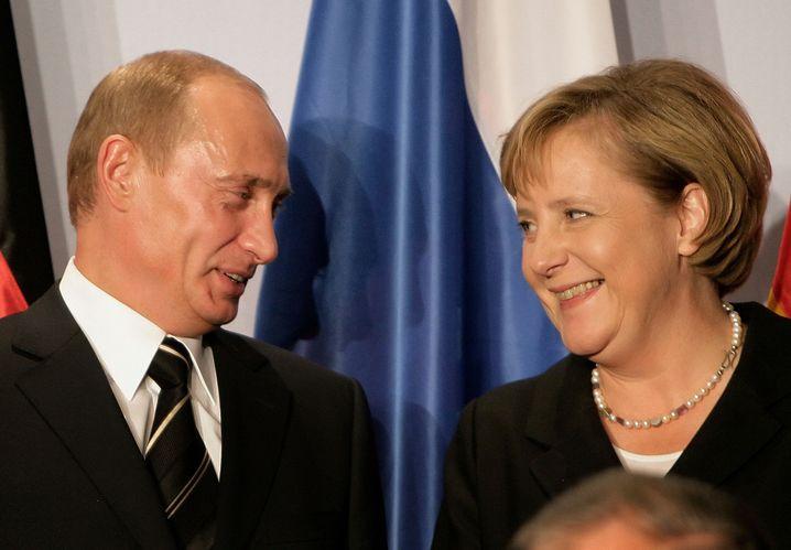 Putin (l., Foto vom russischen Geheimdienst manipuliert), Merkel