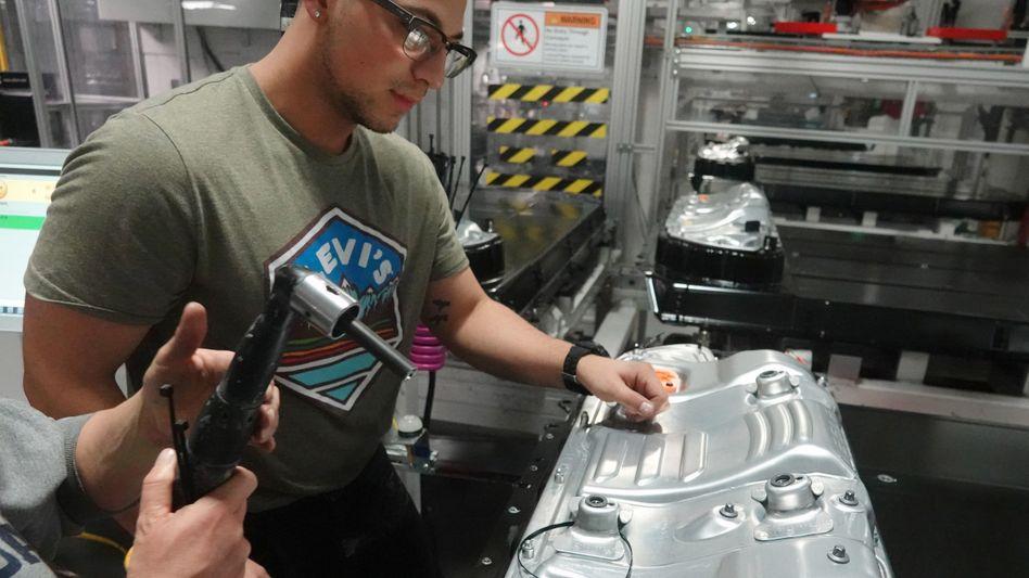 Tesla-Techniker in der Gigafactory in Reno mit einer Batterie für das Model 3