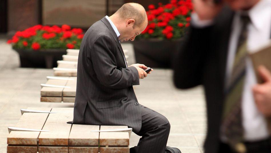 Geschäftsmänner mit Handy: Dominiert von der Angst, etwas zu verpassen