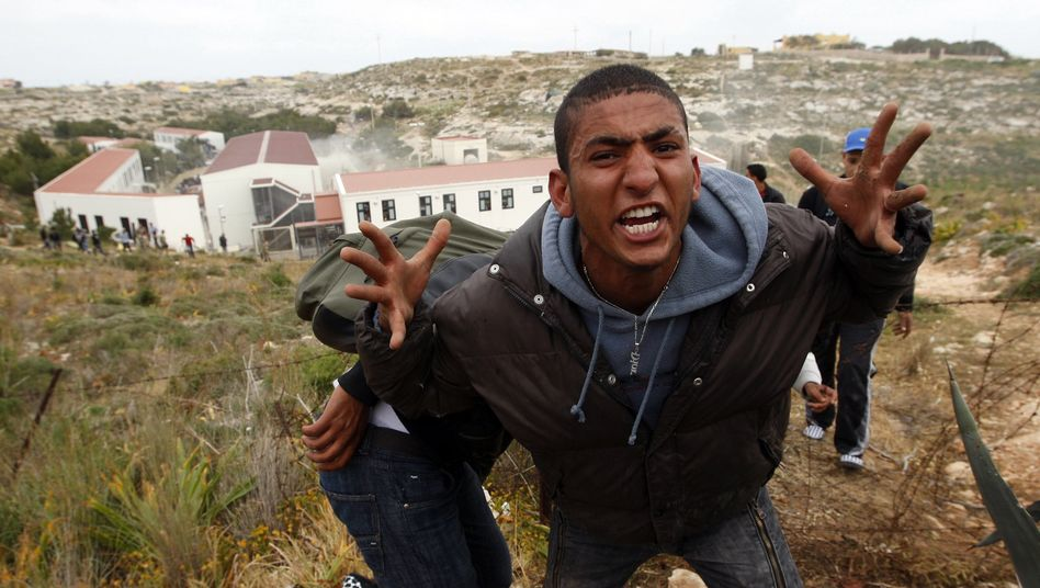 A man who fled the unrest in Tunisia leaves the immigration center on the Italian island of Lampedusa to protest against being sent back to his country.