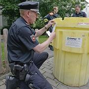 Razzia mit 600 Objekten: Ein Polizeibeamter versiegelt in Hannover eine Tonne mit Chemikalien