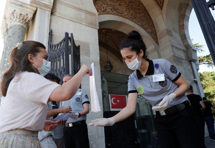 Nur mit Maske und den richtigen Dokumenten: Eine Bewerberin der Universität von Istanbul auf dem Weg zu ihrem Aufnahmetest, den am Wochenende rund 2,4 Millionen Menschen ablegen